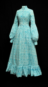 A turquoise and white full-length cotton Laura Ashley dress with a Ram and Pelican pattern and puffed long sleeves, stand up collar, tie belt, flounce at hem. Early 1970s