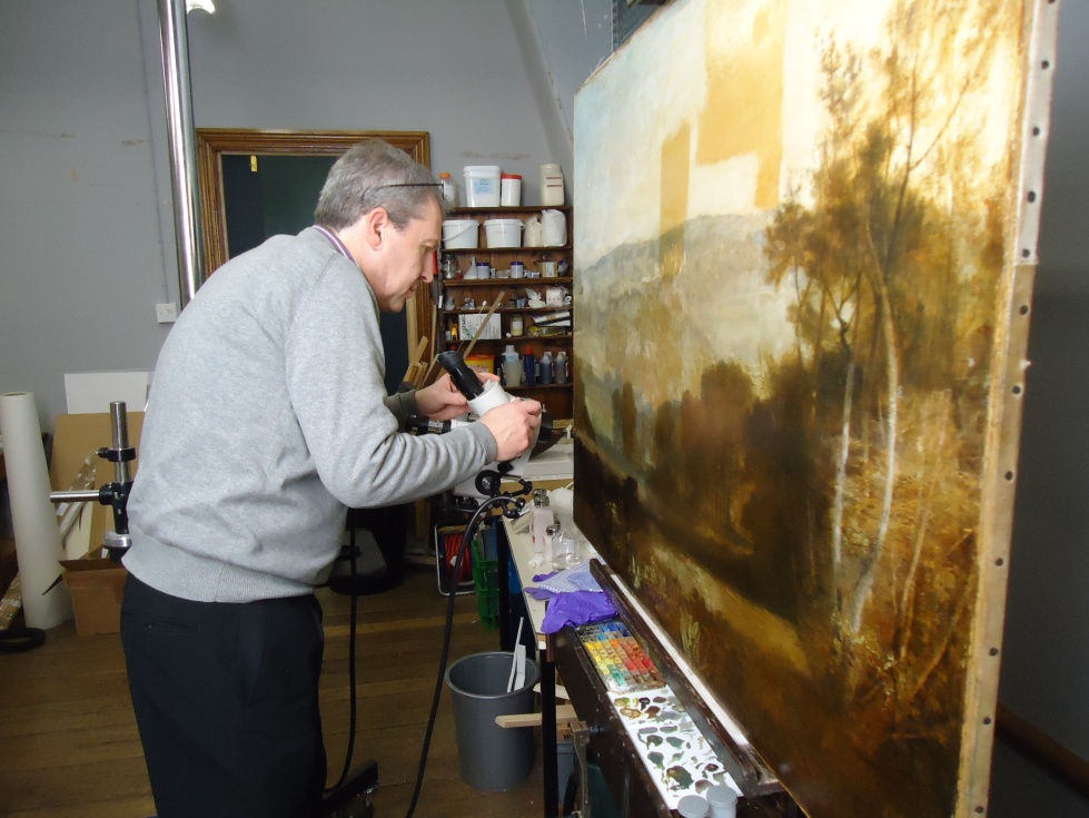 Jon examines the painting in the Conservation Studio