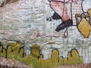 Detail of disordered embroidery threads, with hole in canvas
