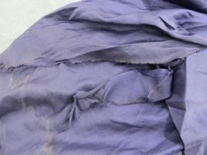 Detail of loose hem, with brown watermark, and tear