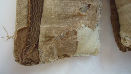 CST.2.976 Close up of previous repairs in undyed cream cotton and grey synthetic thread.
