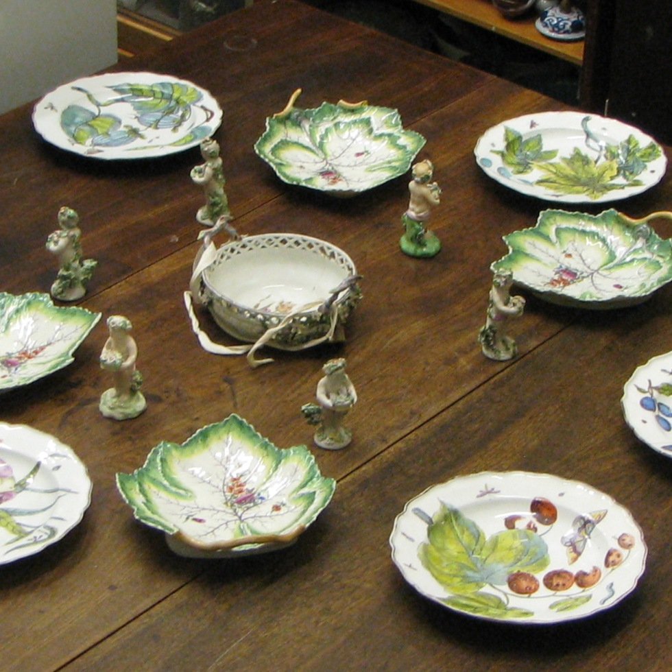 A 'trial' dessert setting from the Bowes Museum stores, featuring Chelsea botanical plates, Worcester leaf dessert dishes, and Derby figures of Cupids