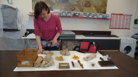Preparing the objects for display: checking and recording their condition,  and removing surface dirt