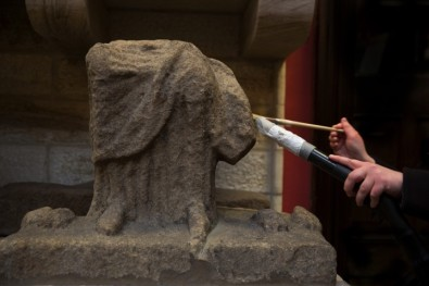The disembodied hands of a conservator, removing dust from a piece of Roman sculpture