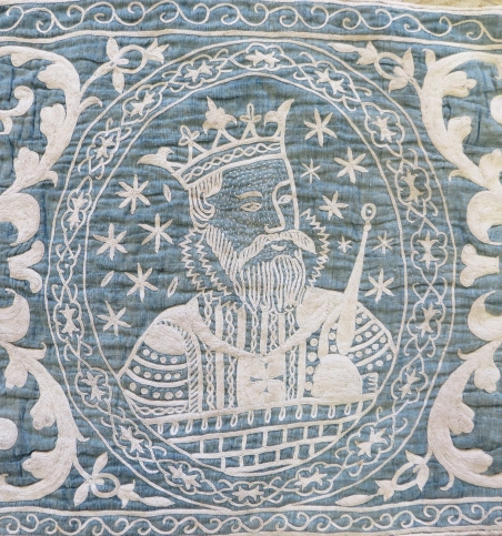 Close-up of a king embroidered in cream cotton thread onto an indigo cotton ground