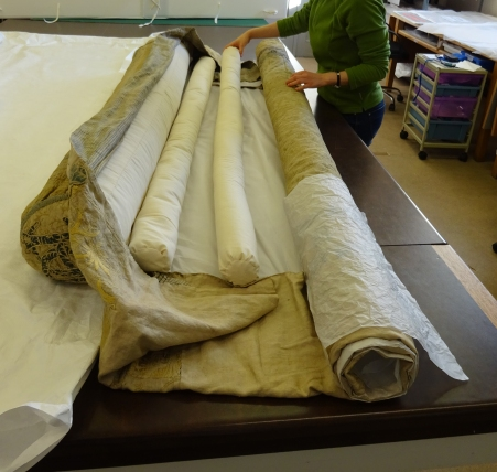 Coverlet being rolled using polyester wadding cushions and interleaved with acid-free tissue