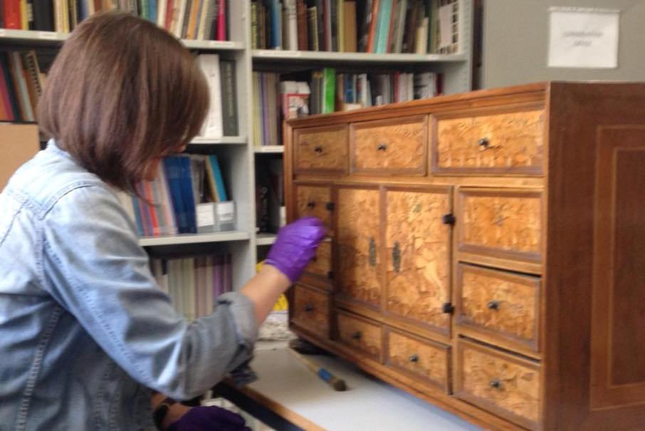 Becky cleaning & condition checking a 16th century veneered cabinet
