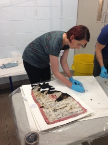 Textiles conservation intern Emily oversees the damaged textiles