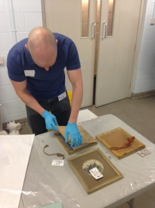 Paintings Conservation intern Paul removes watercolours from their frames