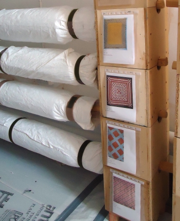 Quilts re-rolled and returned to store, using wooden or metal poles to suspend them in our homemade wooden box system. New object labels with photographs make them easier to identify