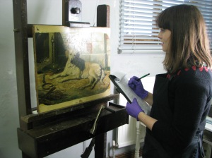 Pauline assesses a painting of Josephine Bowes' dog for loan
